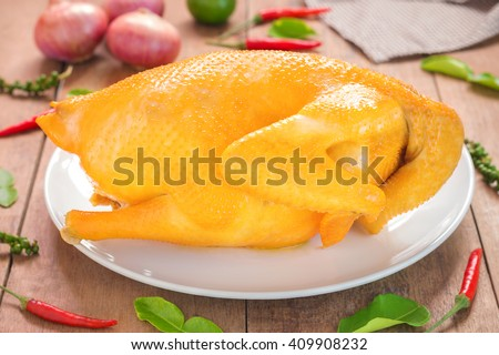 Whole boiled chicken with vegetables on wooden table prepared, Chinese cuisine - stock photo