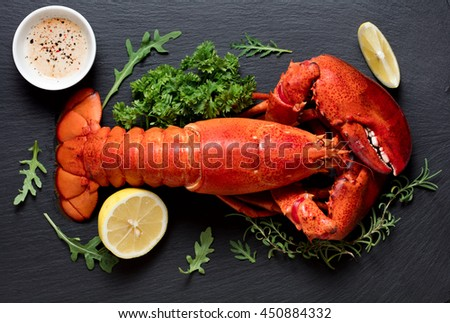 Whole boiled lobster on black slate plate - stock photo