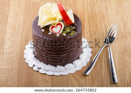 Whole Chocolate Cake on Wooden Table - stock photo