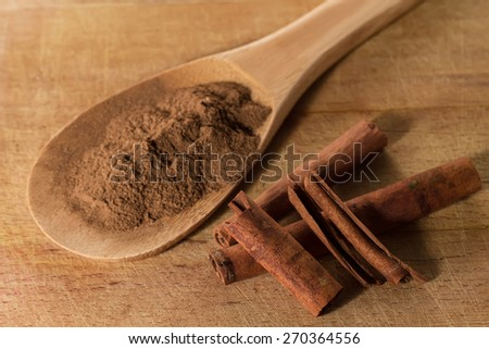 Whole cinnamon sticks and cinnamon powder in spoon on wooden background - stock photo