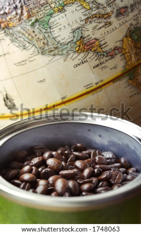 Whole coffee beans in a can, with a map of Central America in soft focus in the background. - stock photo