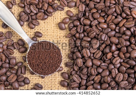 Whole Coffee Beans on Burlap with Ground Coffee in Spoon - stock photo