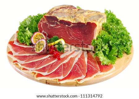 Whole cured, dried serrano ham with thin slices arranged on board. Isolated on white. - stock photo