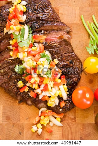 Whole flank steak served with corn salsa - stock photo