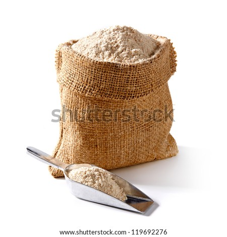 Whole flour in bag with scoop on white background - stock photo