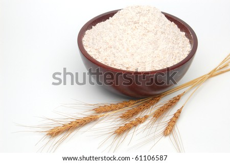Whole flour in bowl with wheat ears on white - stock photo