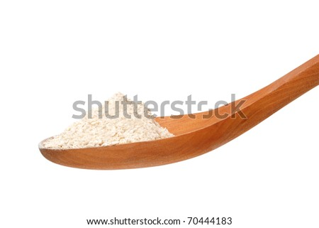 Whole flour in spoon from side on white background - stock photo