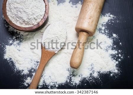 Whole flour in spoon on dark vintage background - stock photo