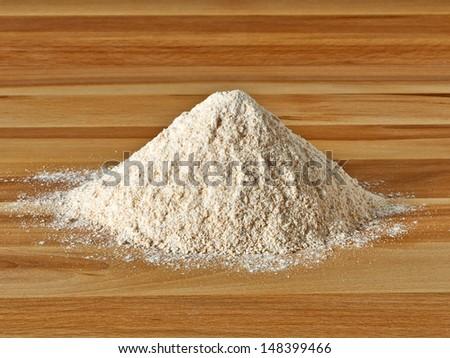 Whole flour pile on wooden background - stock photo