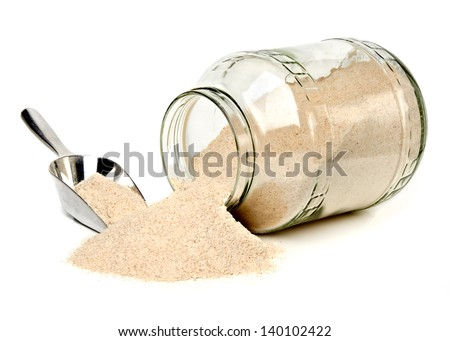 Whole flour spread from jar with scoop on white background