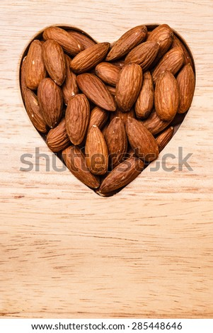 Whole food, good for health. Heart shaped almonds on wooden surface board background