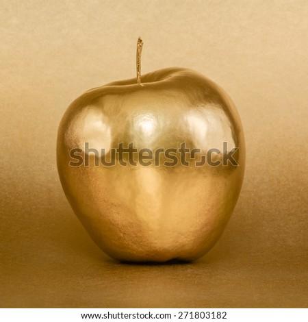 Whole golden apple on gold background - stock photo