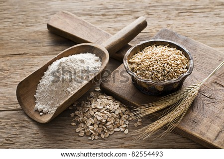 Whole grain and flour on wooden background close up - stock photo