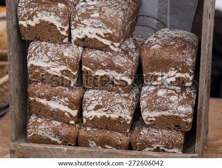 Whole Grain Bread Loaves in a Rustic Wooden Crate in a Food Market. - stock photo