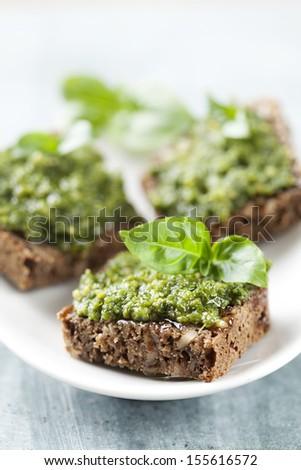 whole grain bread with fresh basil pesto - stock photo