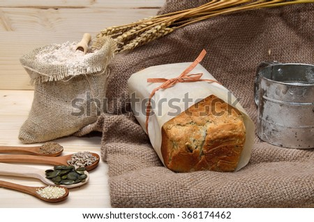 Whole grain bread with healthy ingredients, spoons of pumpkin, flax, sunflower and sesame seeds and sack of flour - stock photo