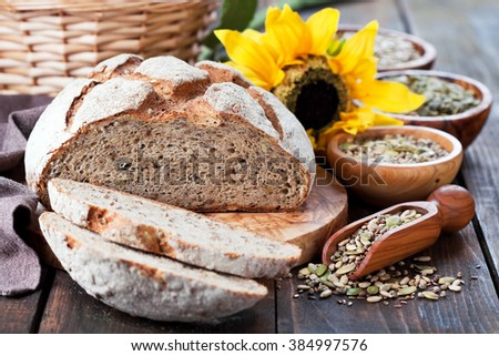 Whole grain bread with seeds of sunflower, pumpkin, flax and hemp, selective focus - stock photo
