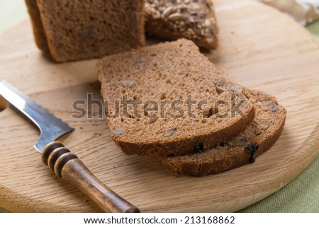 Whole grain brown bread on cutting board - stock photo