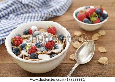 Whole-grain flakes with fresh berries in bowl and yogurt on wooden background
