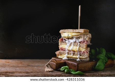 Whole grain grilled sandwich bread with melting hot cheese, ham, basil and pouring white sauce on wooden chopping board over dark background. With copy space