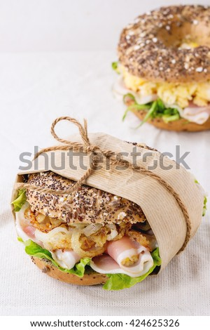 Whole Grain papered bagels with fried onion, scrambled eggs, green salad and prosciutto ham over white linen tablecloth. - stock photo