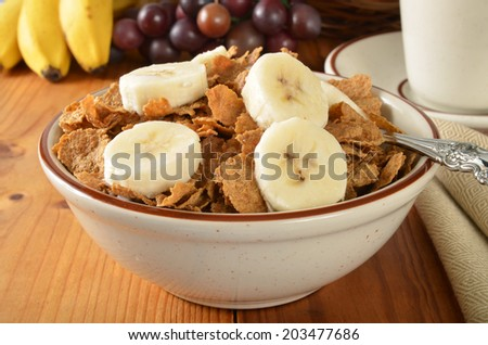 Whole grain wheat cereal with bran and sliced bananas - stock photo