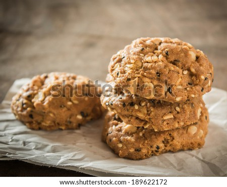 Whole grains cookies on paper with wooden background.
