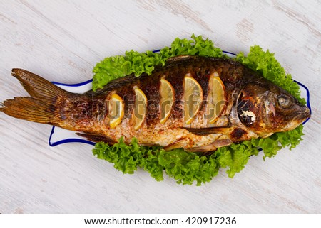 Whole grilled fish carp served with salad and lemon; glass of wine