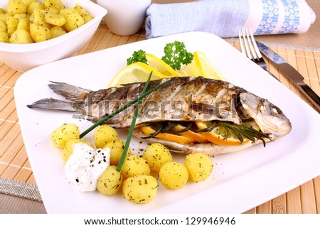 Whole grilled fish served with potatoes, sauce and lemon