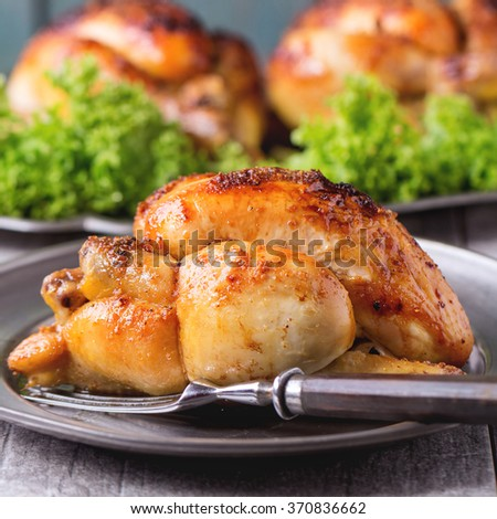 Whole Grilled mini chicken on vintage metal plate and dish with chicken and green salad behind over whitw wooden table. Square image with selective focus - stock photo