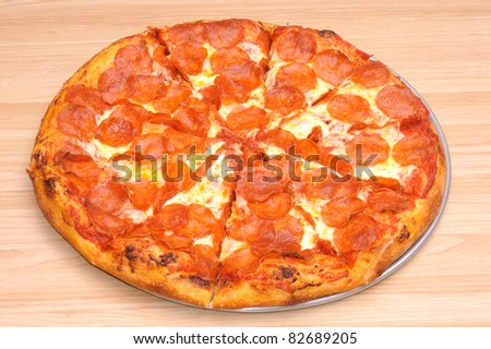 whole Pepperoni pizza on a pan sitting on a table in closeup - stock photo