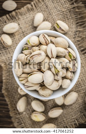 Whole Pistachios on wood as detailed close-up shot (selective focus) - stock photo