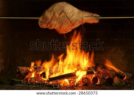 Whole pork leg grilled in fire - stock photo