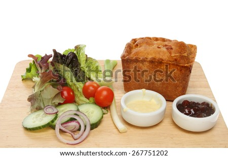 Whole pork pie with salad, pickle and salad cream on a wooden board - stock photo