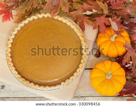 Whole pumpkin pie with two pumpkins and autumn leaves - stock photo