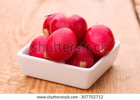 whole radish in white porcelain bowl on wood
