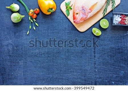 Whole raw fish (Nile tilapia) with lime, herbs and spices. Bell pepper, cherry tomato, young garlic on a dark wooden board. Space for text. - stock photo