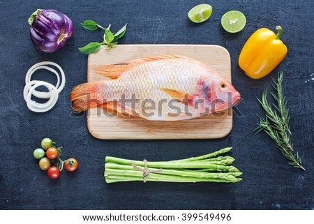Whole raw fish with lime and herbs. Farm vegetables (asparagus, eggplant, bell pepper, cherry tomato, onion) on a dark wooden board. Cooking background. Healthy food / diet concept.  - stock photo