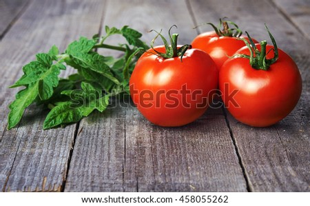 whole red tomatoes and tomatoes green leaves on wooden table