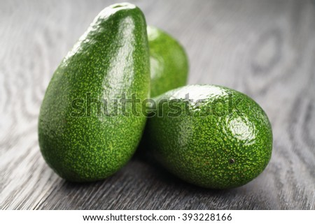 whole ripe green avocados on wood table, selective focus - stock photo