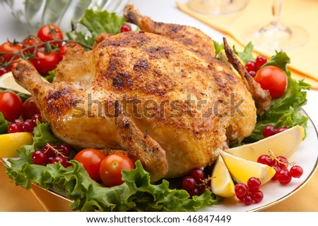 Whole roasted chicken garnished with fresh cucumbers, wine tomatoes, green salad and sage on dinner table