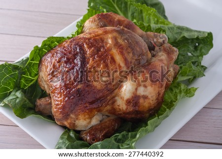 whole roasted chicken on white serving plate with green lettuce