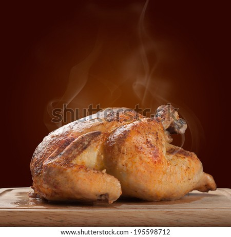 Whole roasted chicken on wooden board - stock photo
