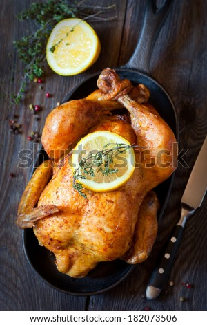 Whole roasted chicken with lemon and thyme on a pan. Rustic style. - stock photo