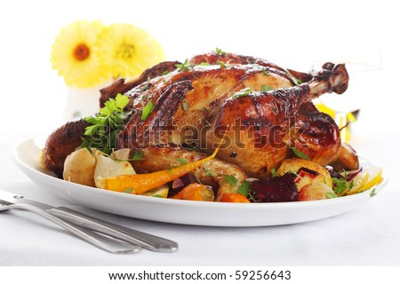 Whole roasted chicken with vegetables on a white plate - stock photo