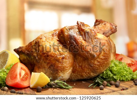 Whole roasted chicken with vegetables on plate, on wooden table in cafe