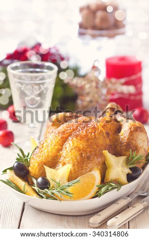Whole roasted orange chicken with fruit garnish and rosemary for Christmas dinner. - stock photo