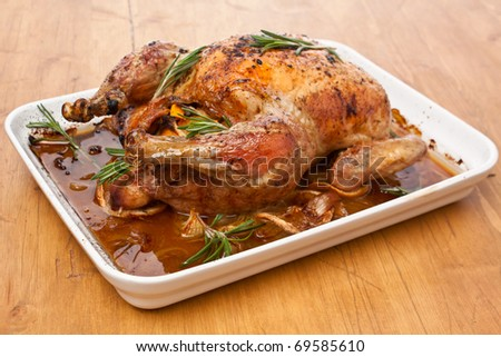 whole roasted stuffed chicken in a dish on a wooden table - stock photo
