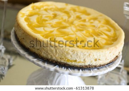 Whole Swirled Mango Cheesecake on a White Flowered Cakeplate - stock photo
