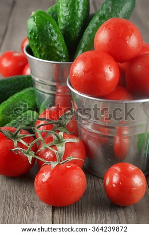 Whole wet tomatoes and cucumbers in galvanized buckets on rustic wooden table.
